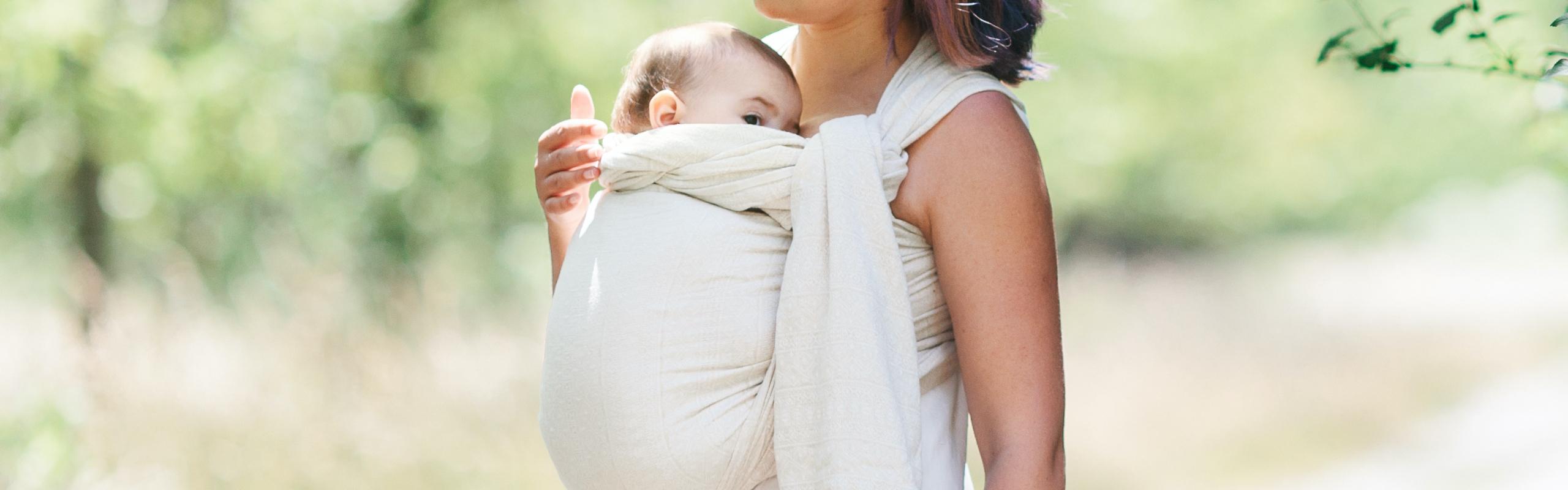 Photo d'une maman portant sont bébé en SLING